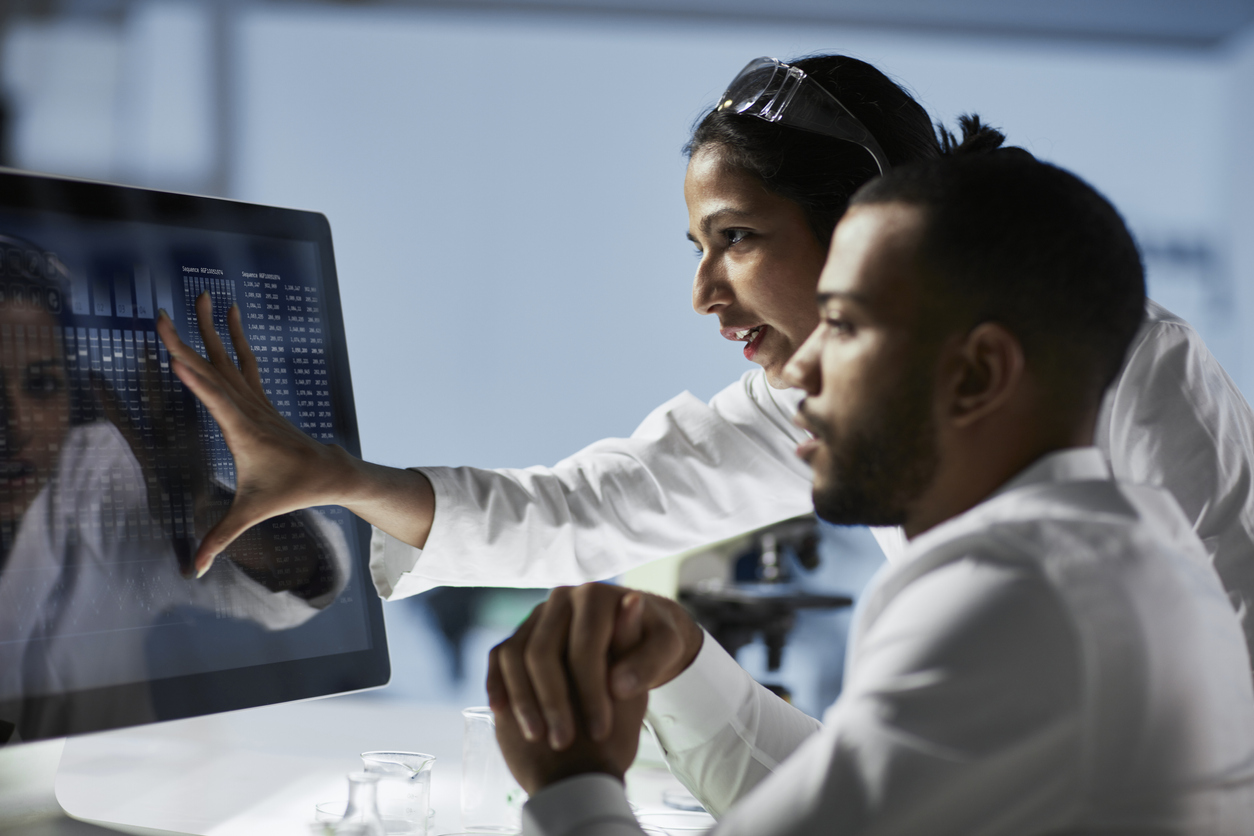 scientists looking at data on computer screen, data analytics in medicine concept