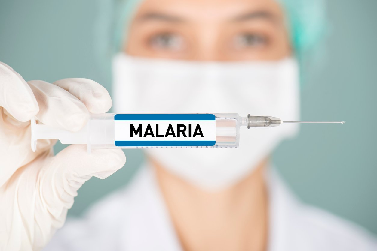 Doctor holding up needle with the word Malaria written on it